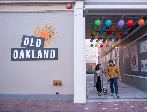A couple walks a dog through a tunnel next to a sign that says Old Oakland