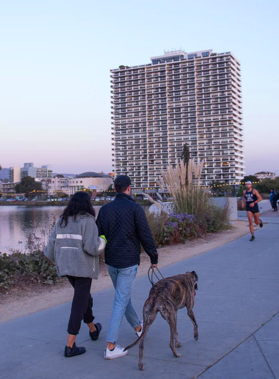 A couple walking a dog, a jogger and other pedestrians around Lake Merritt in Oakland
