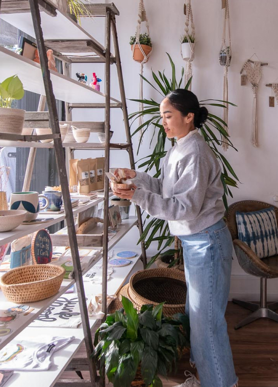 Woman holding a bowl filled with products at a boutique in Old Oakland