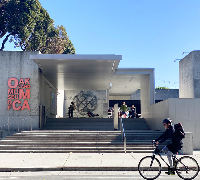 A bicyclist passing in front of the entrance to the Oakland Museum of California